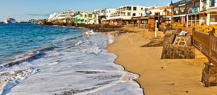 Beach in Lanzarote, beach huts line the sand